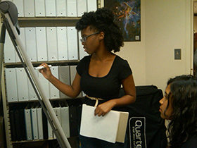 Student writing on an easle in front of white binders on a shelf
