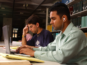 A student listening to ear buds is typing at a laptop as a student in the background touches his own forehead